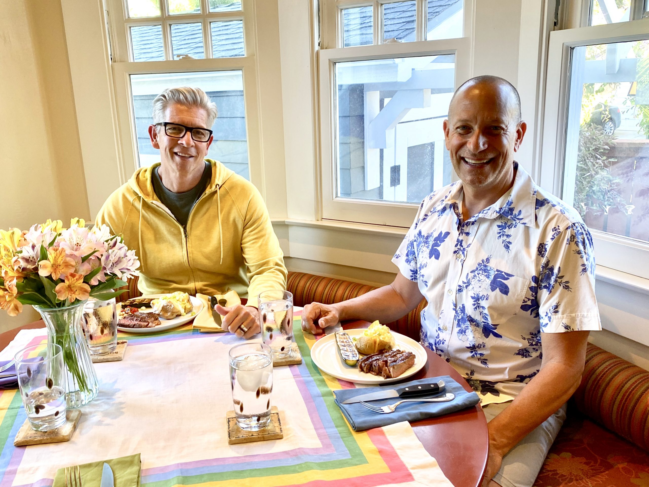 two gay men smile at camera from dinner table at home with steaks and baked potatoes