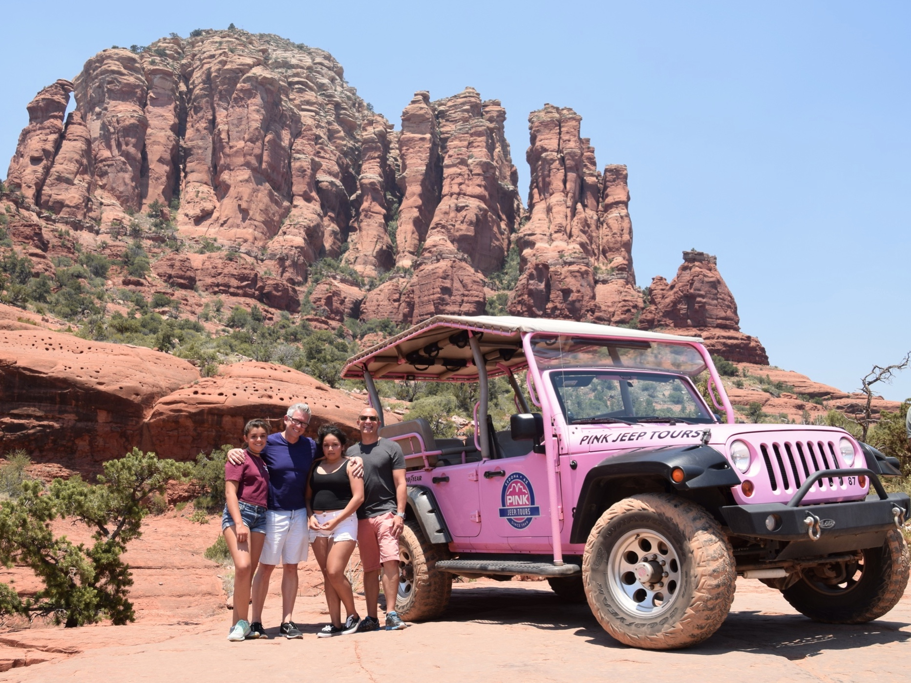 Family posing with red rock formations on Pink Jeep Tours in Sedona, Arizona