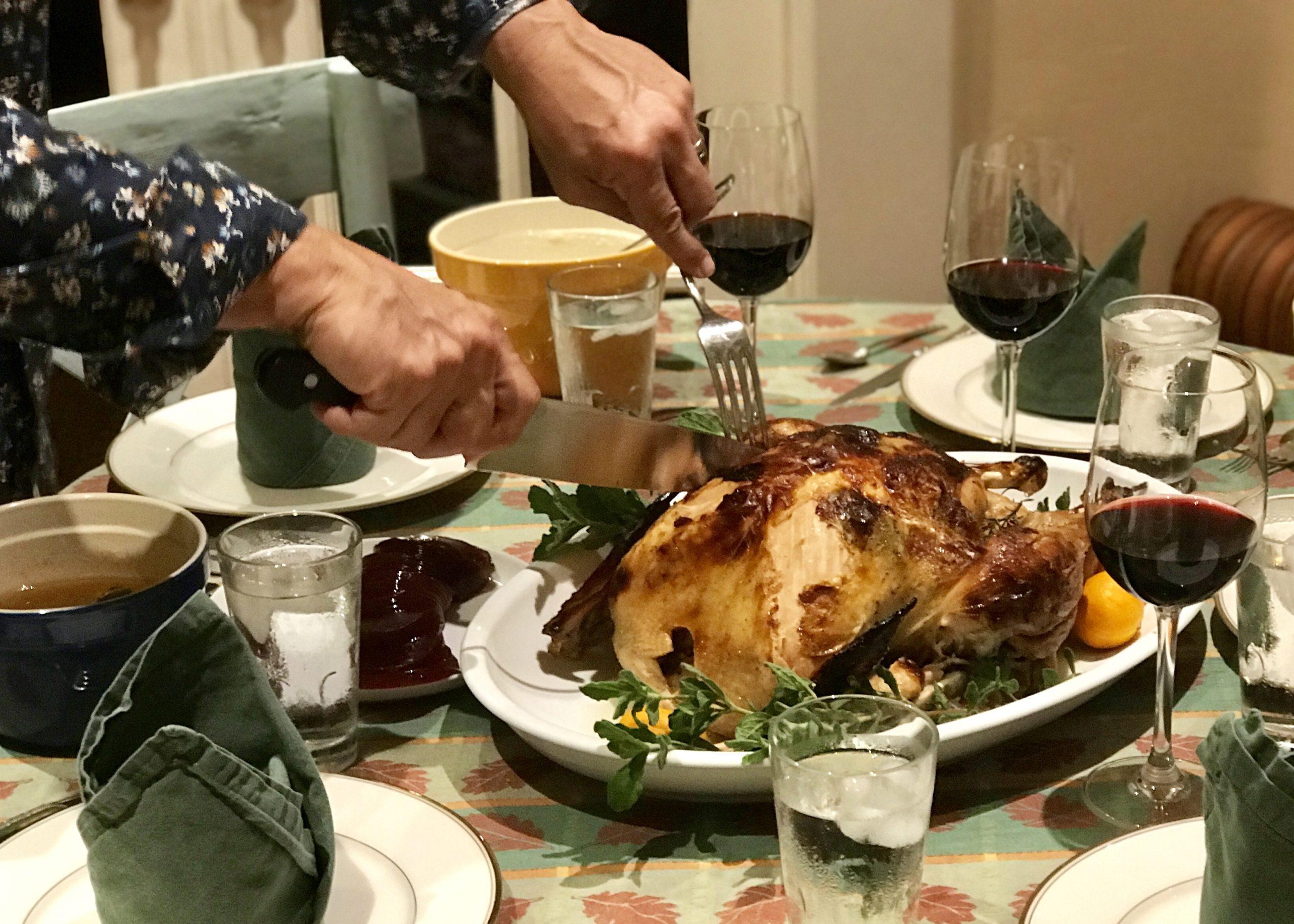 Man carves turkey at Thanksgiving dinner table