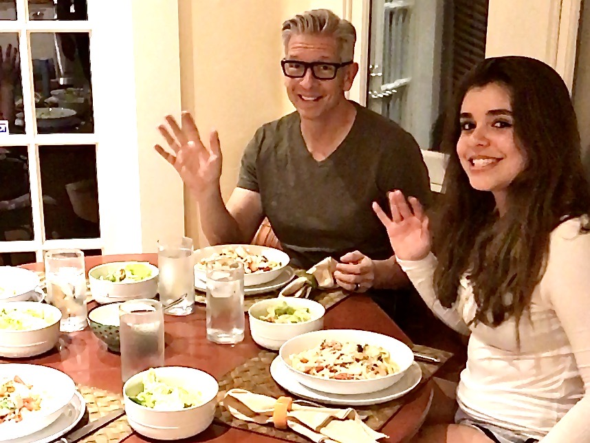 Man and daughter wave at camera from dinner table