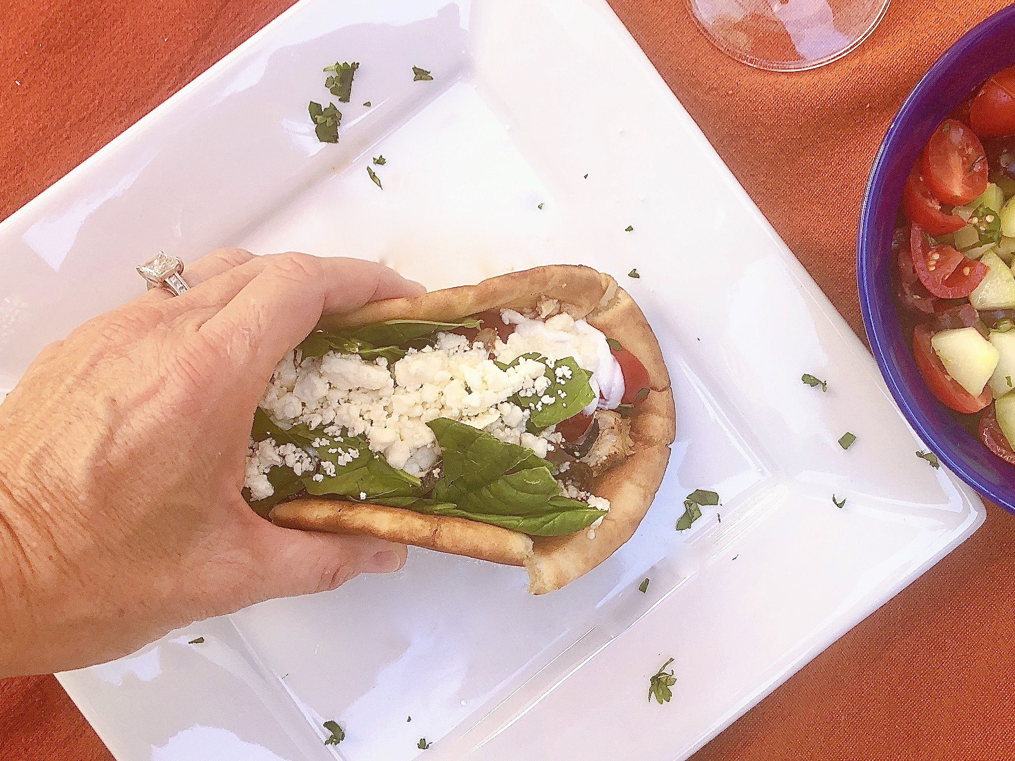 Folded Chicken Gyro Pita Wrap with tomato and cucumber salad folded in woman's hand and ready to eat