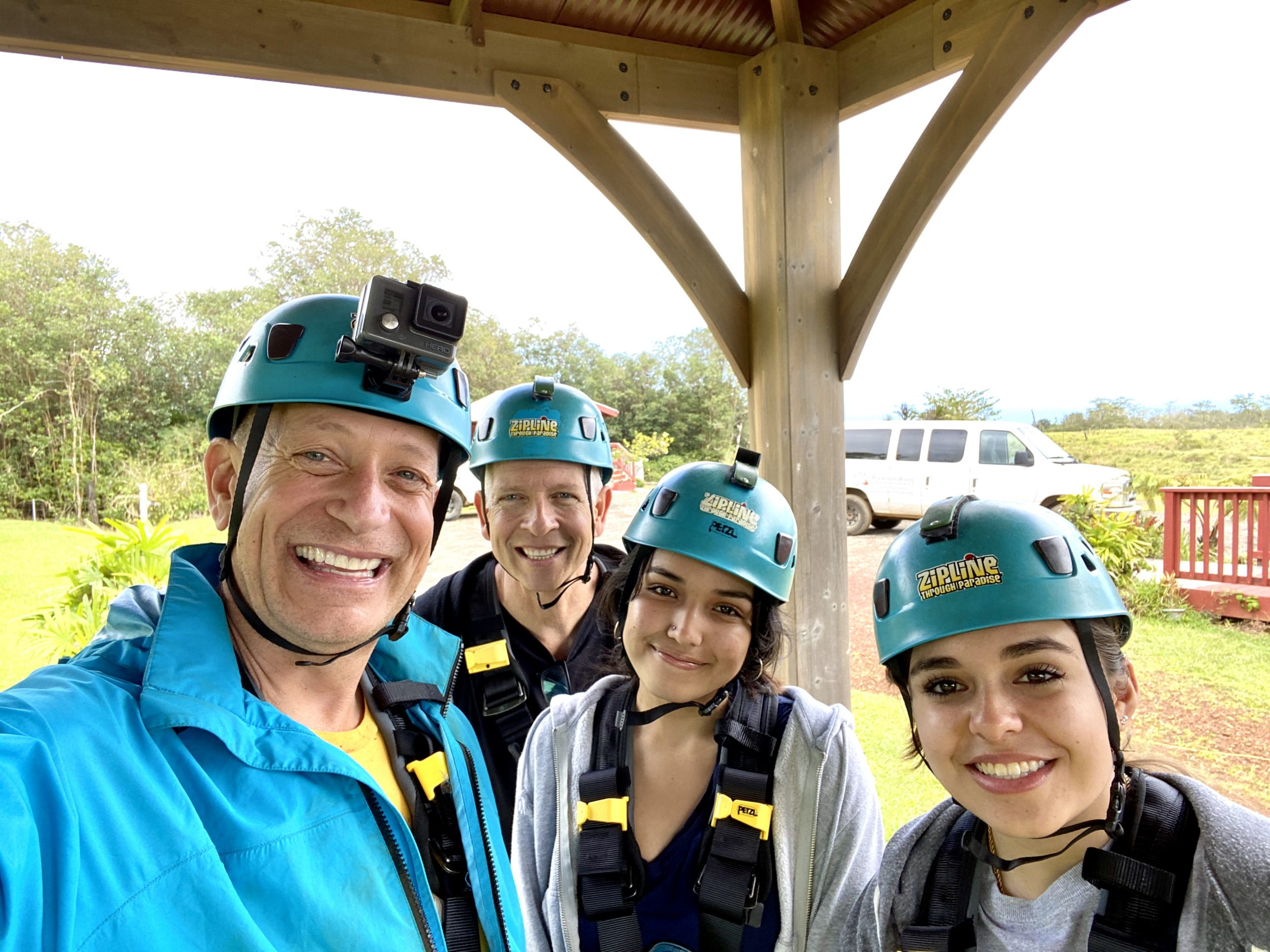 family with two dads in zipline helmets and gear with Kapohokine Adventures near Hilo, Hawaii
