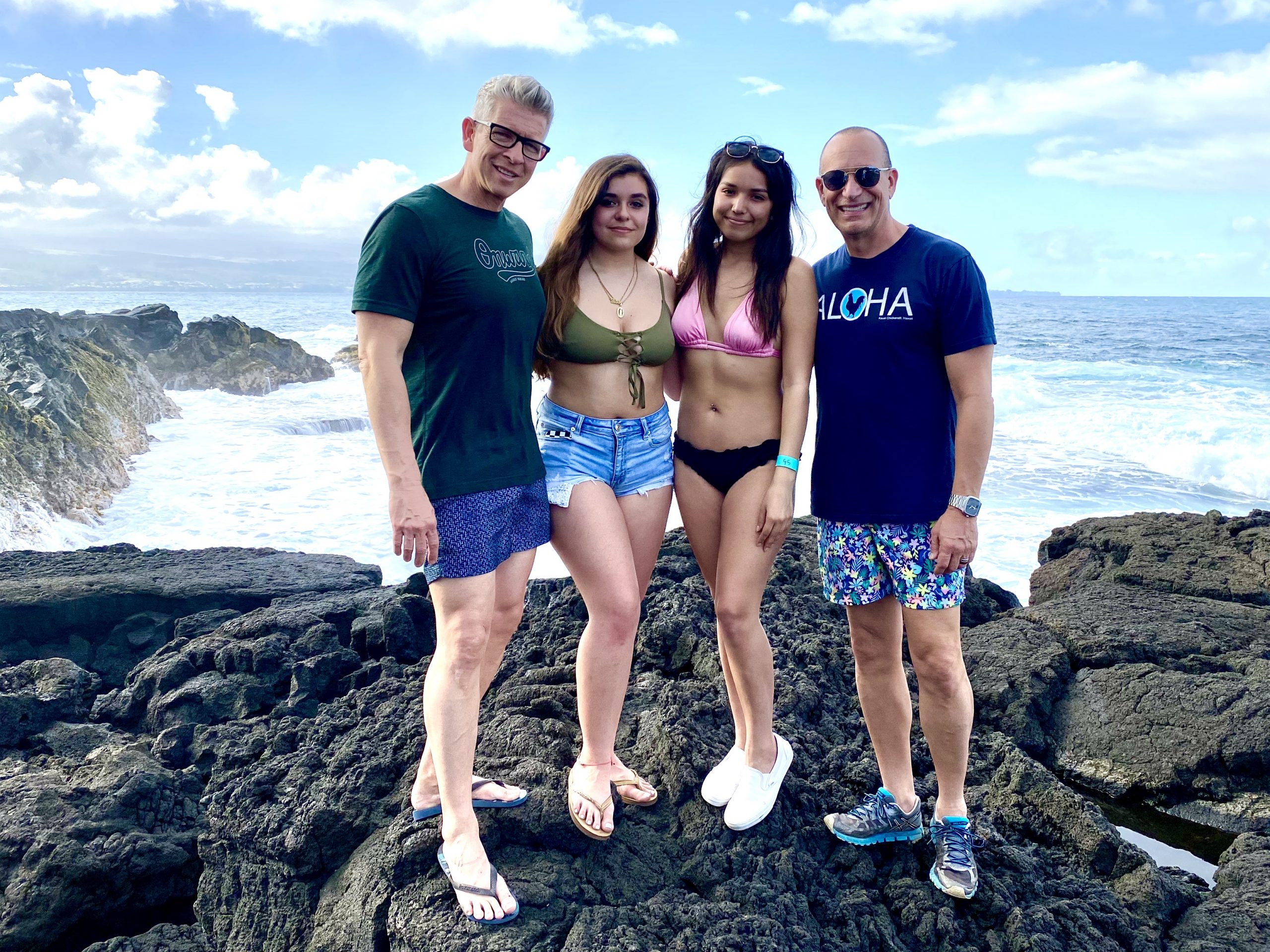gay family with two dads and two daughters poses on lava rocks near ocean in Hilo, Hawaii