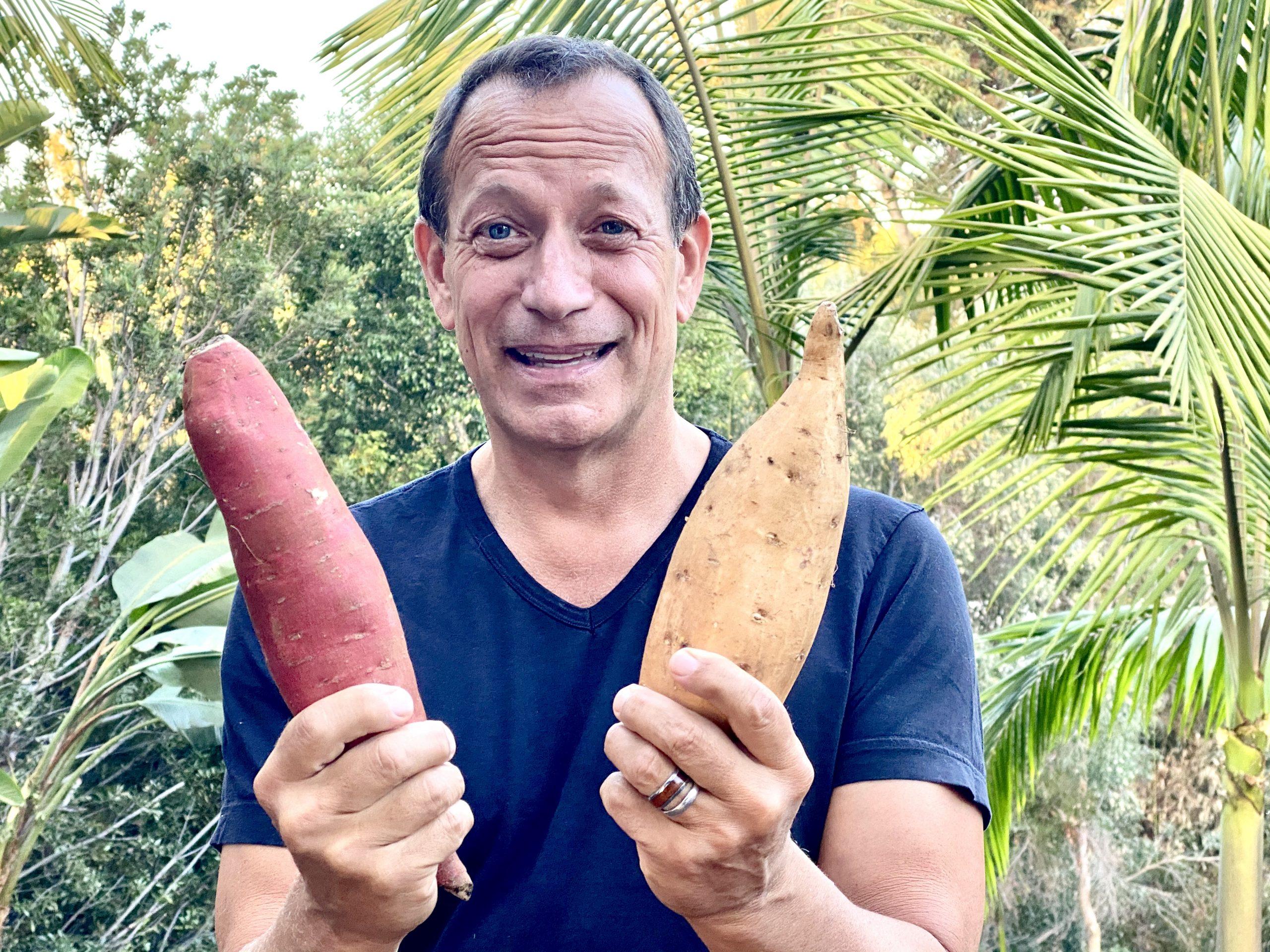 Man holding a sweet potato and a yam