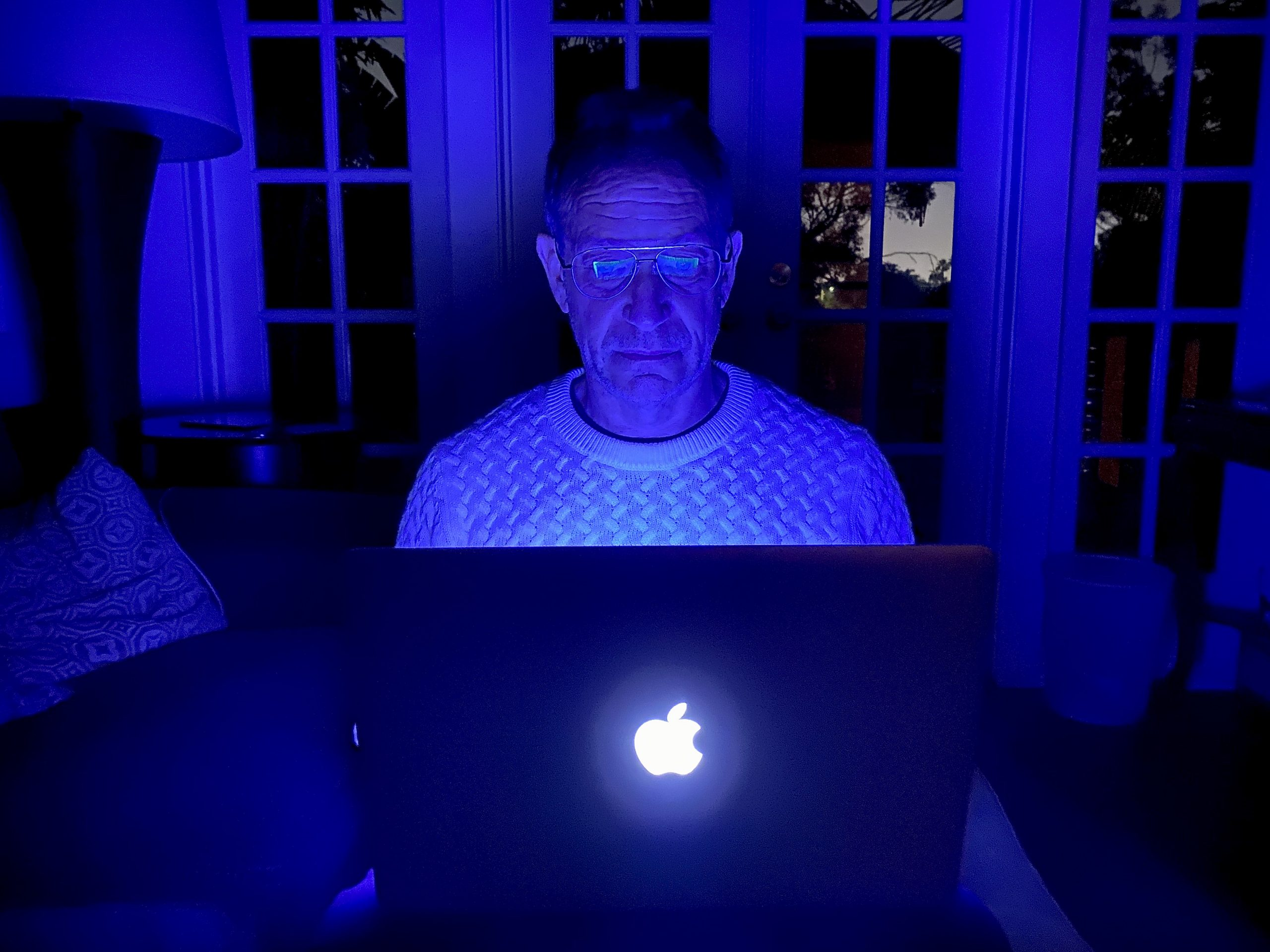 Man staring at laptop computer in blue light with Fashionable Zenni Blokz lenses in an aviator style.