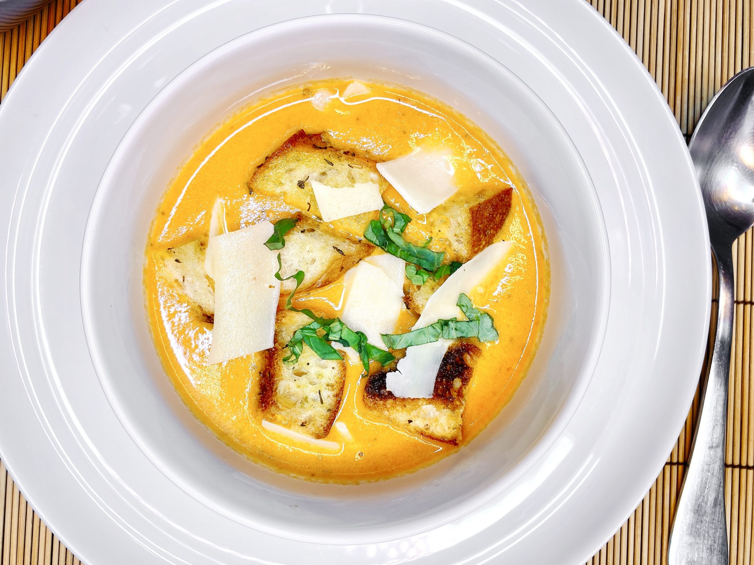 tomato soup recipe shot from above topped with shaved parmesan, basil and croutons