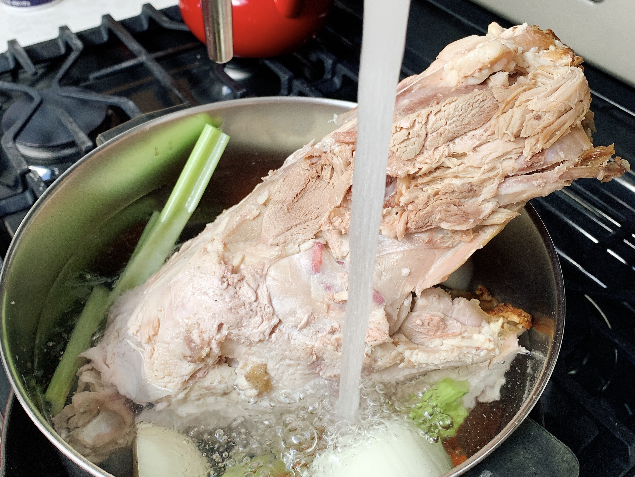 soup pot with running water and ingredients to make turkey stock