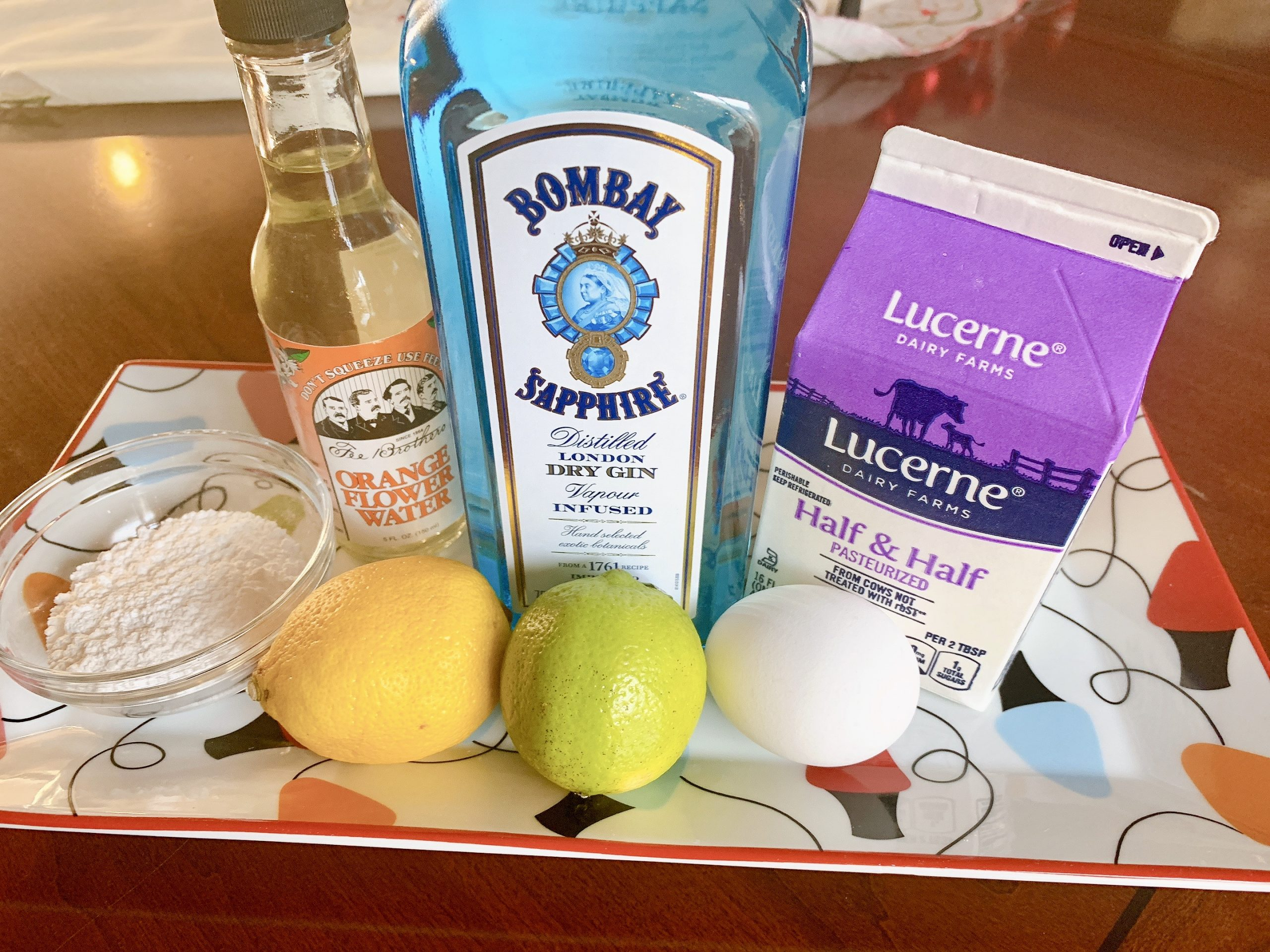 Bombay Sapphire Gin, half and half, egg, orange flower water, powdered sugar, lemon and lime ingredients to make a Holiday Gin Fizz.