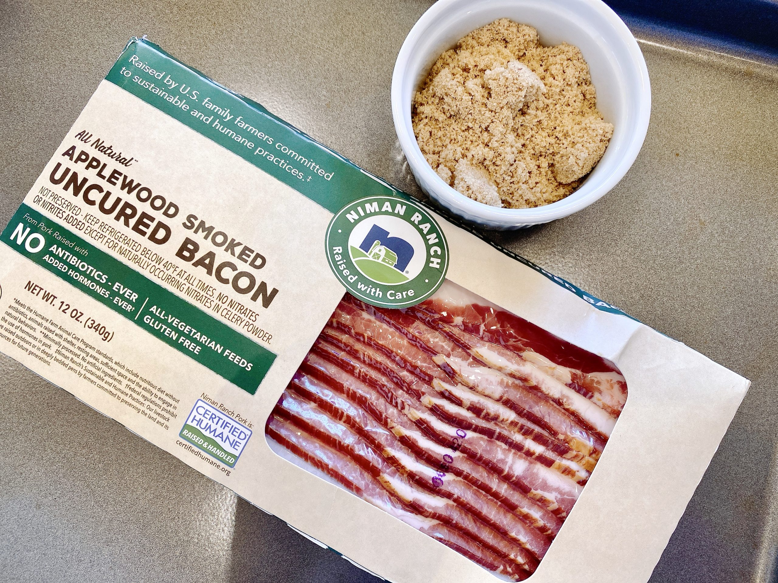 Package of Niman Ranch Applewood Smoked Uncured Bacon on pan with dish of brown sugar