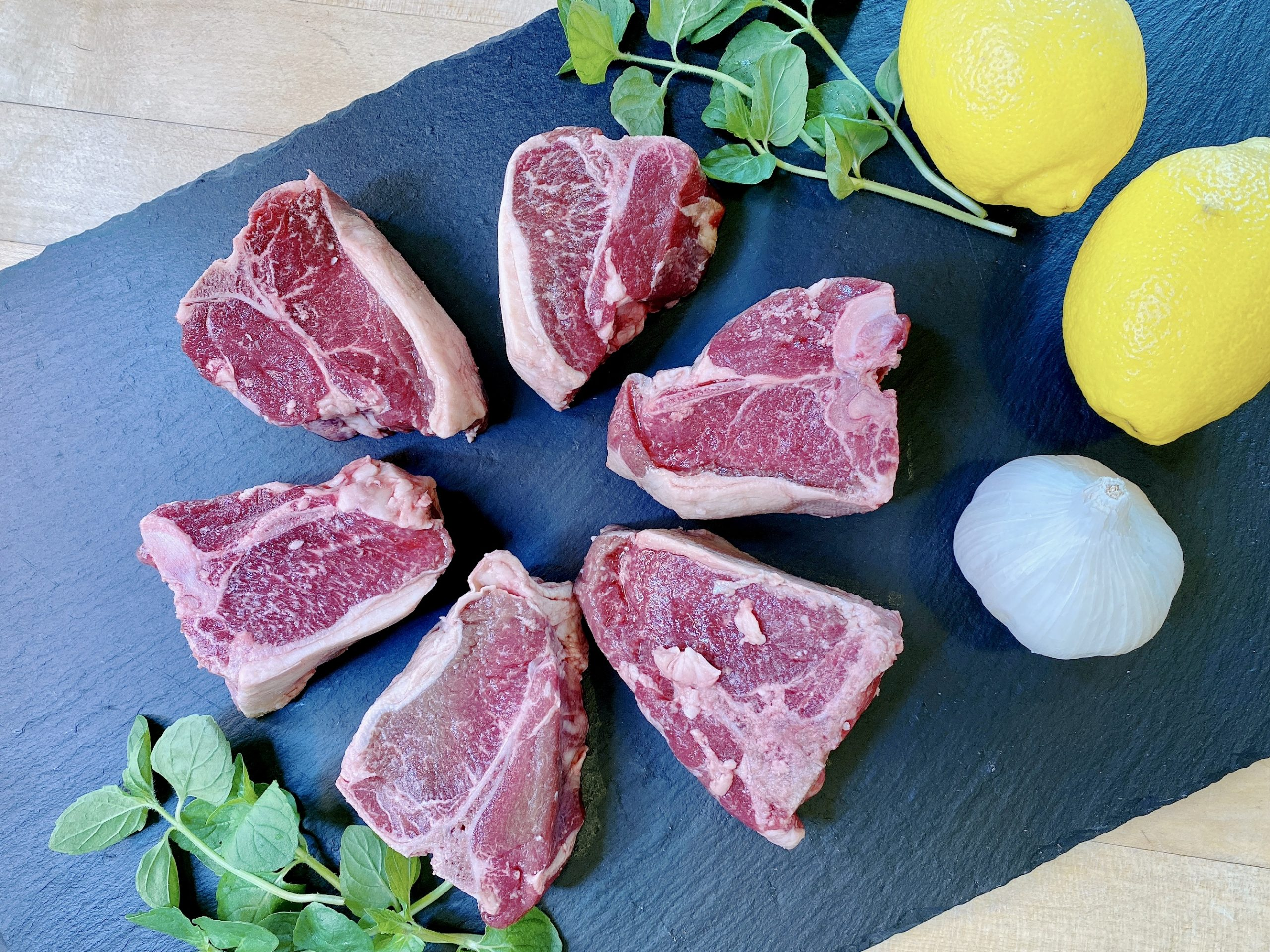 uncooked lamb chops arrange in star pattern on black background with lemon, garlic and mint