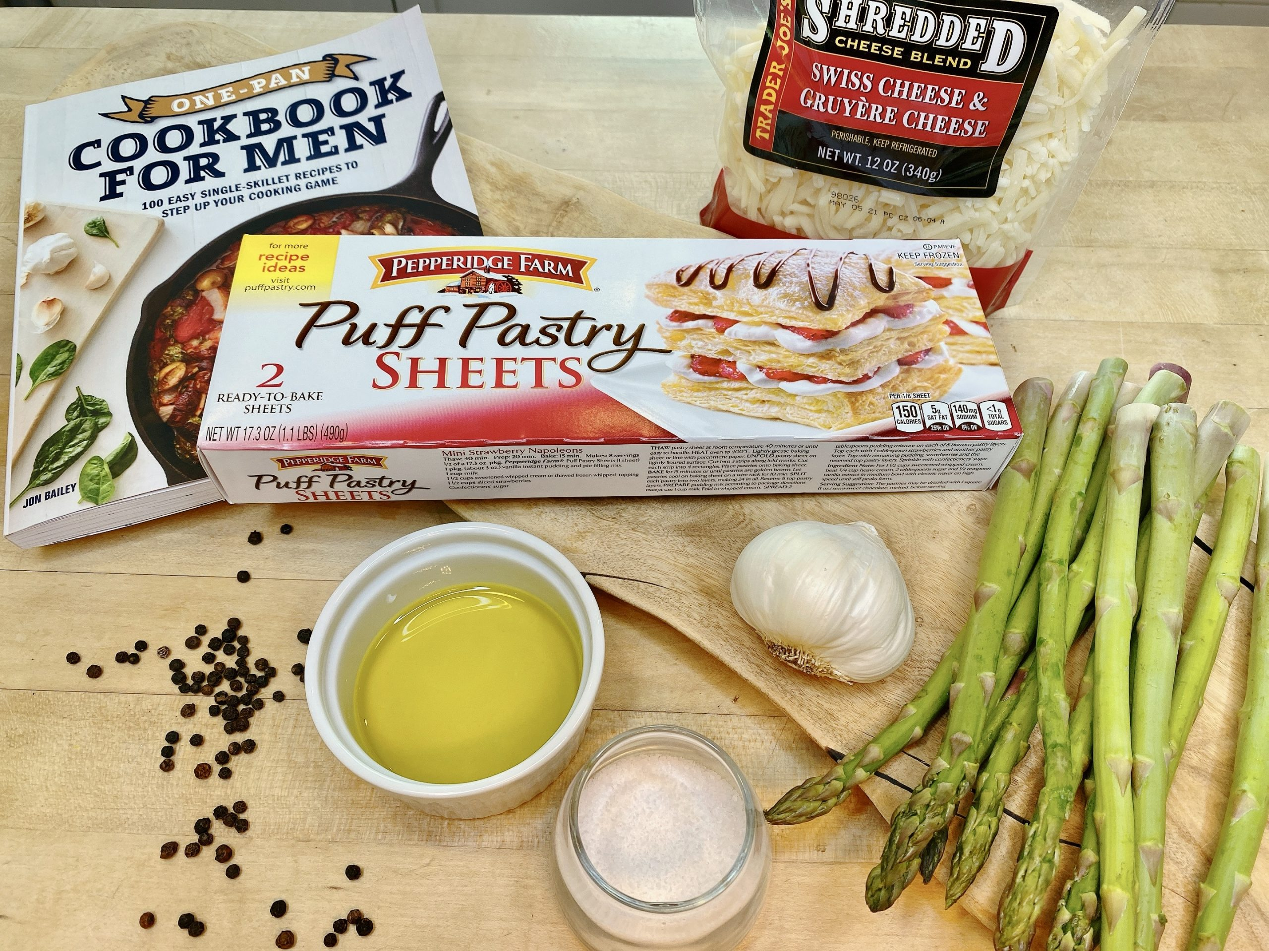 ingredients to make asparagus tart including puff pastry dough, shredded cheese, olive oil, garlic and asparagus