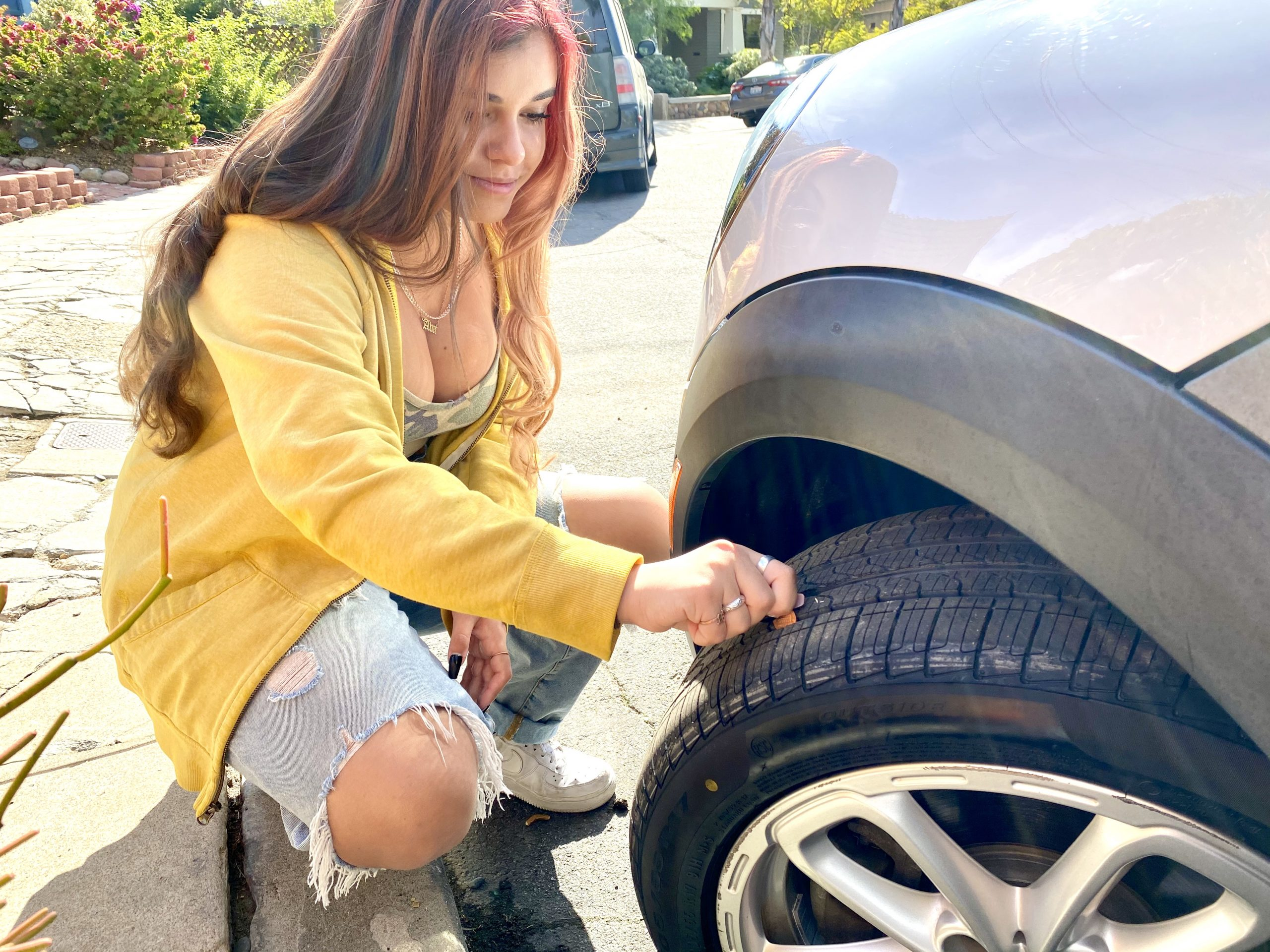 Girl tests depth of tire tread with penny inserted into groove