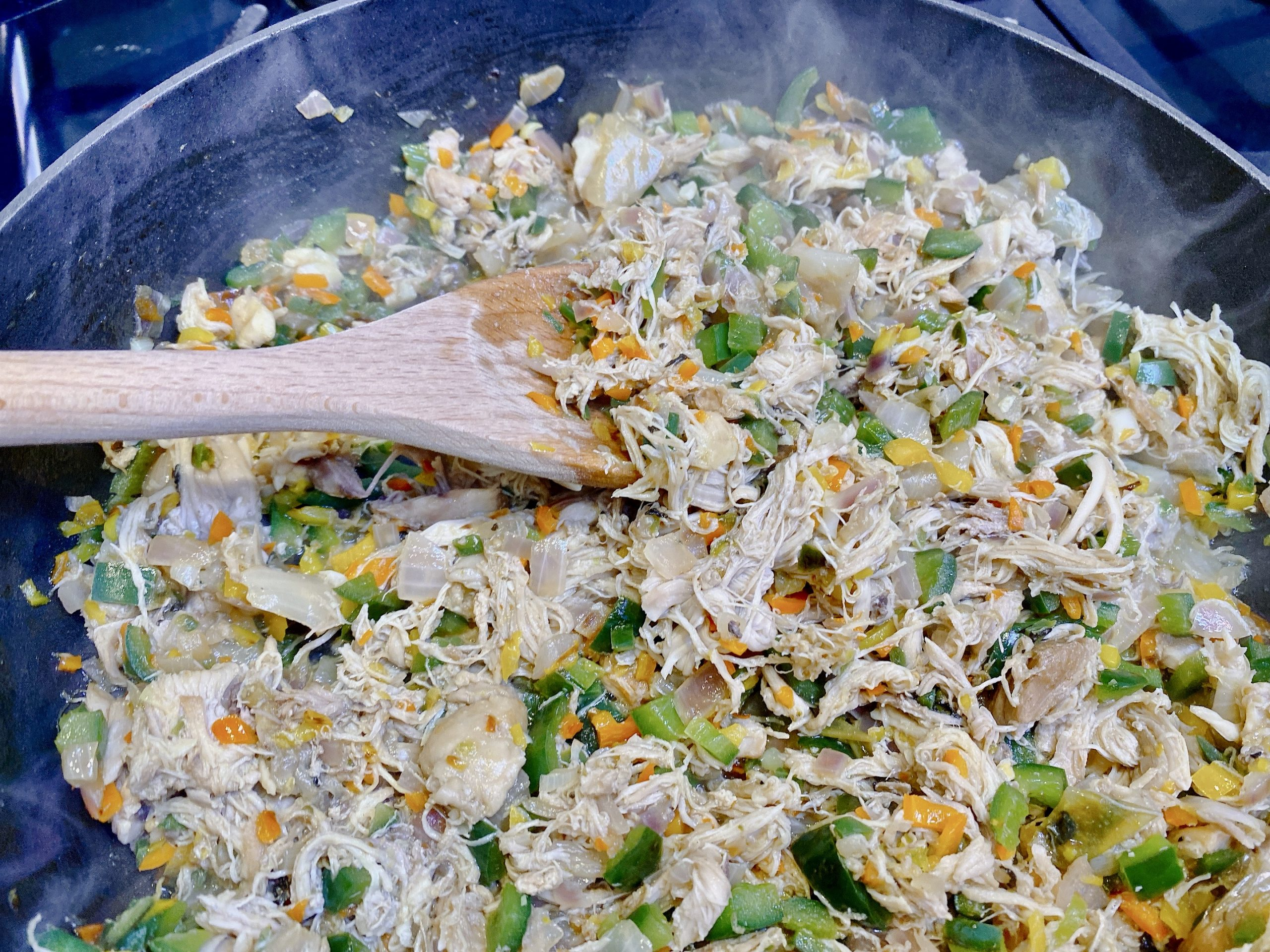 stirring chicken flauta stuffing in pan over stove with wooden spoon