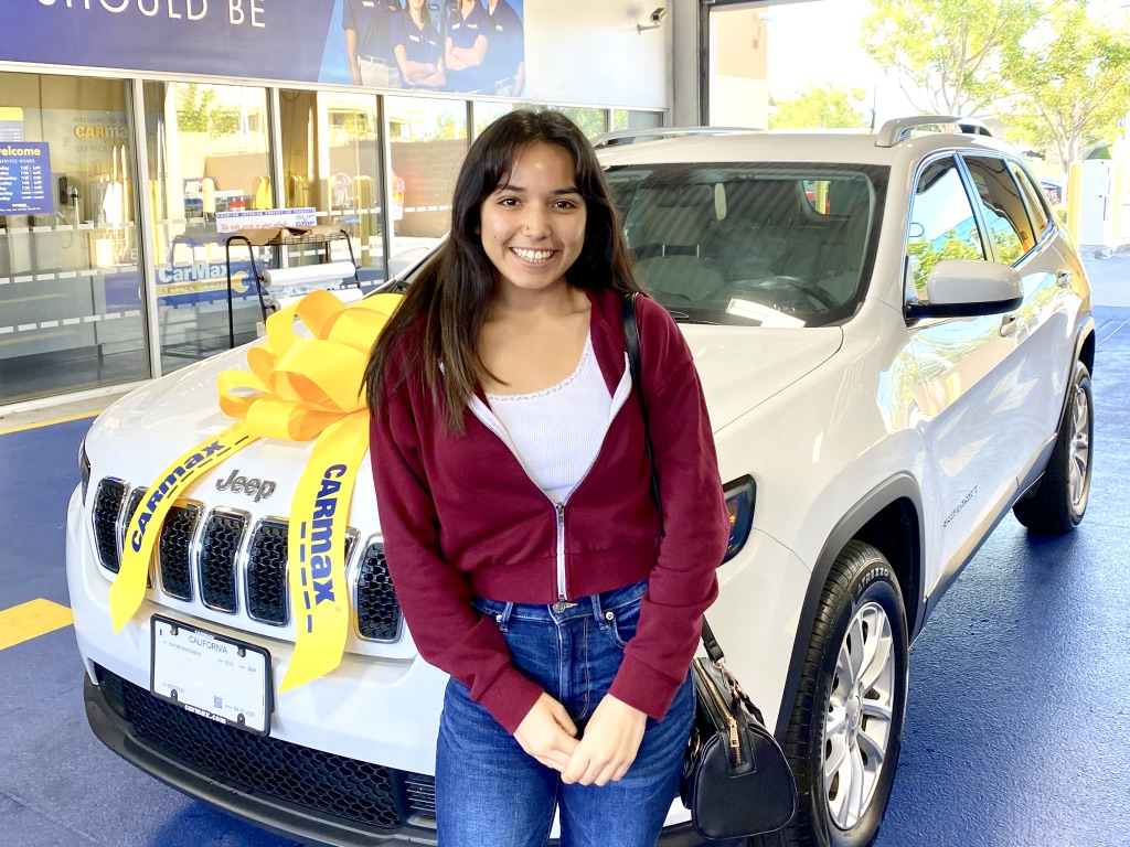 Young woman stands with new Jeep Cherokee from Carmax including big yellow bow of congratulations.