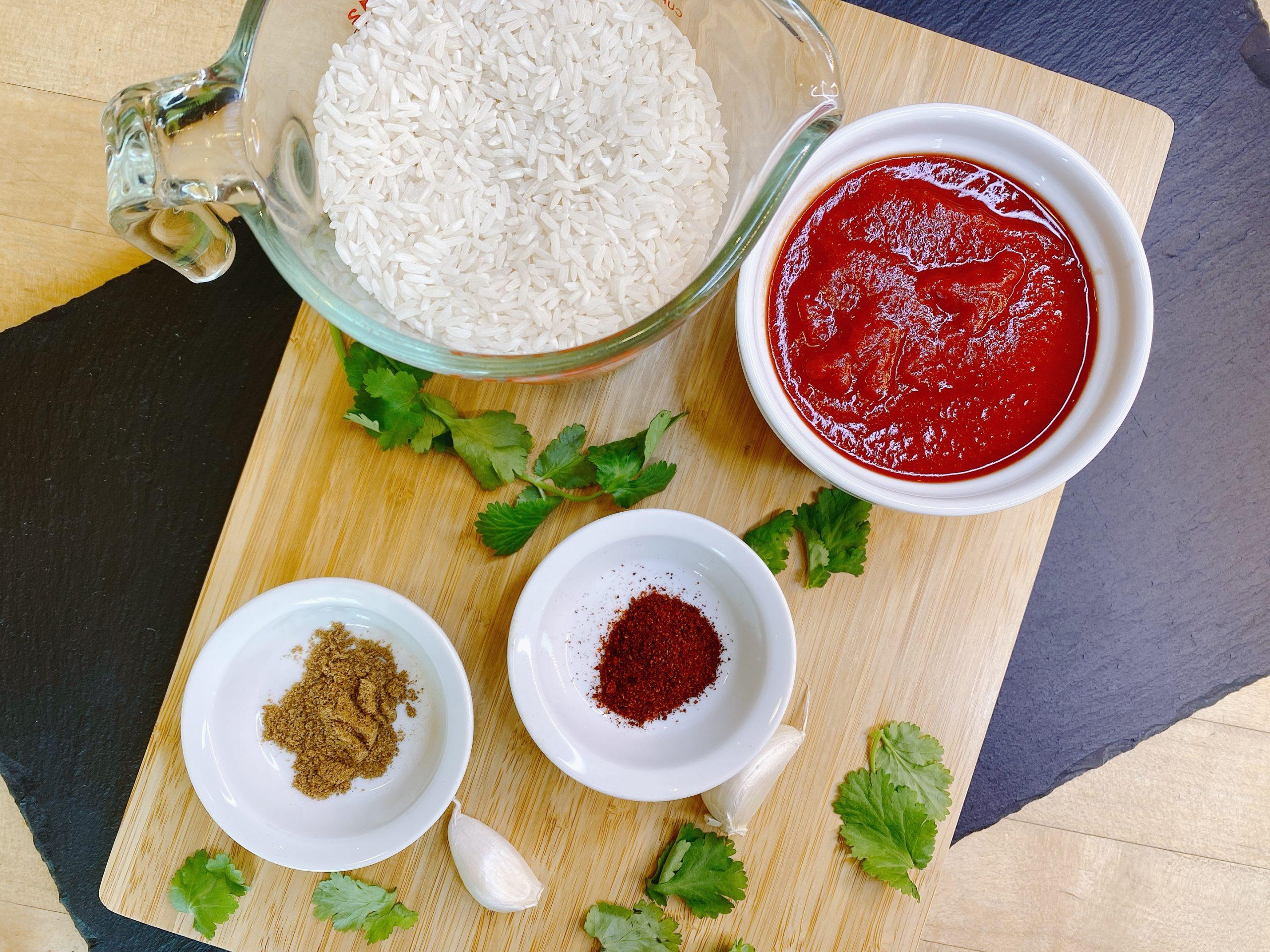 bowls of raw rice, tomato sauce, chili powder and cumin