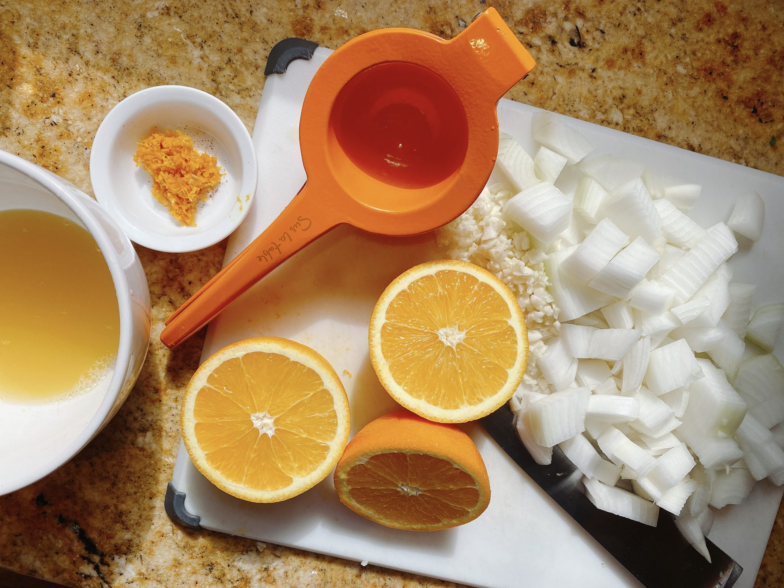 orange juicer with orange halves alongside chopped white onion and garlic