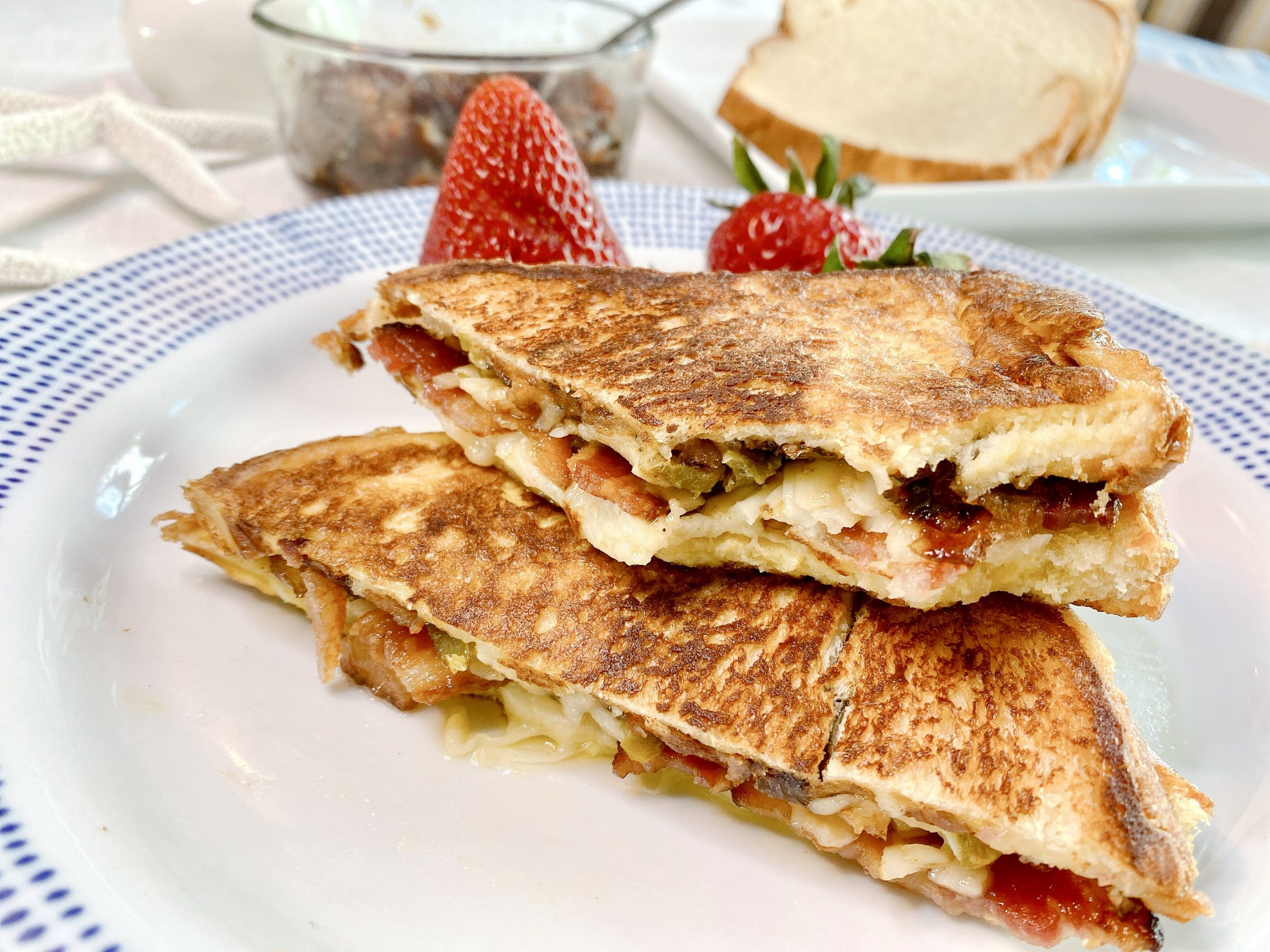Monte Cristo sandwich stuffed with Bacon Jam, presented on plate with fresh strawberries