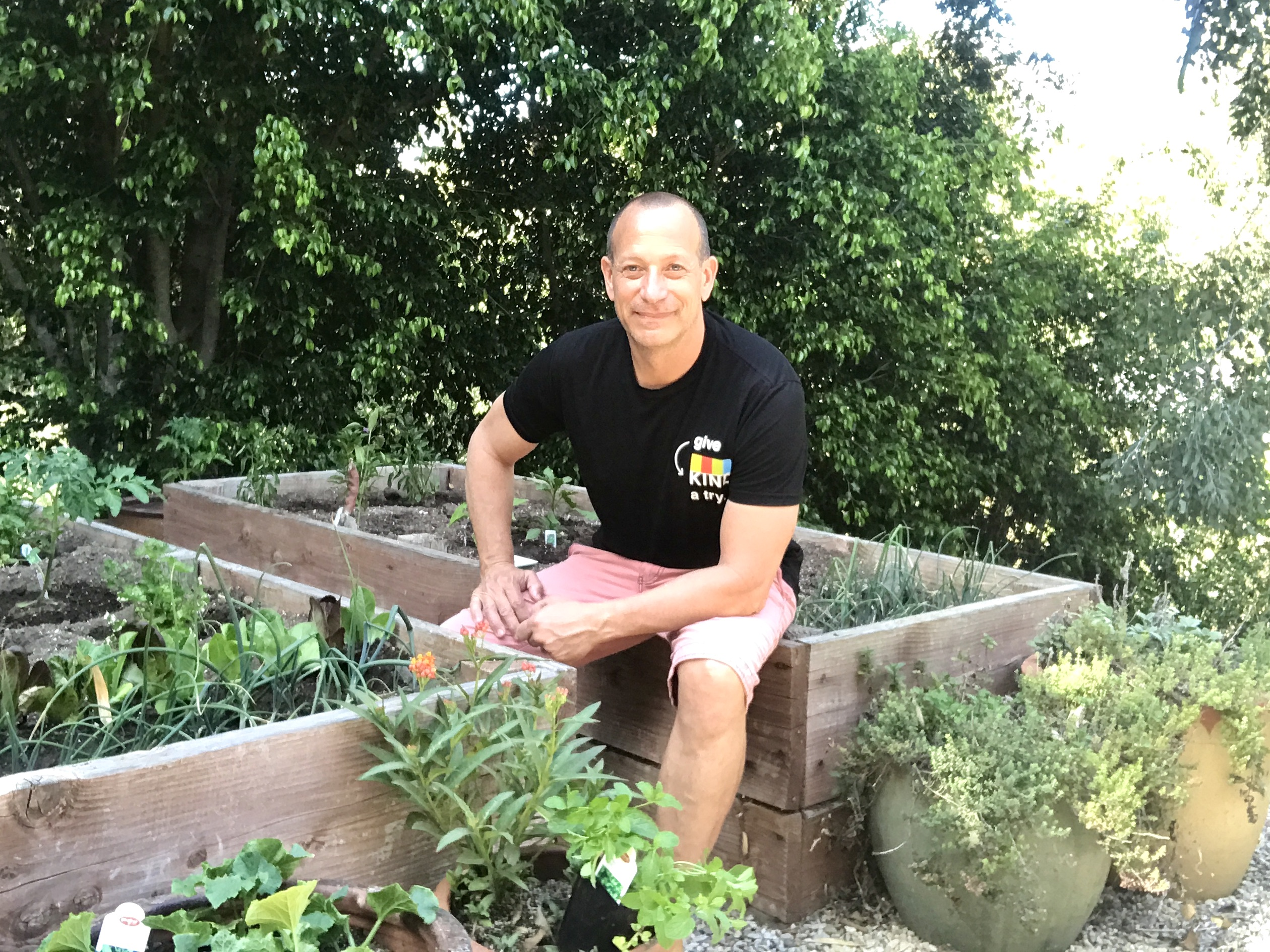 man sits in vegetable garden on raised beds