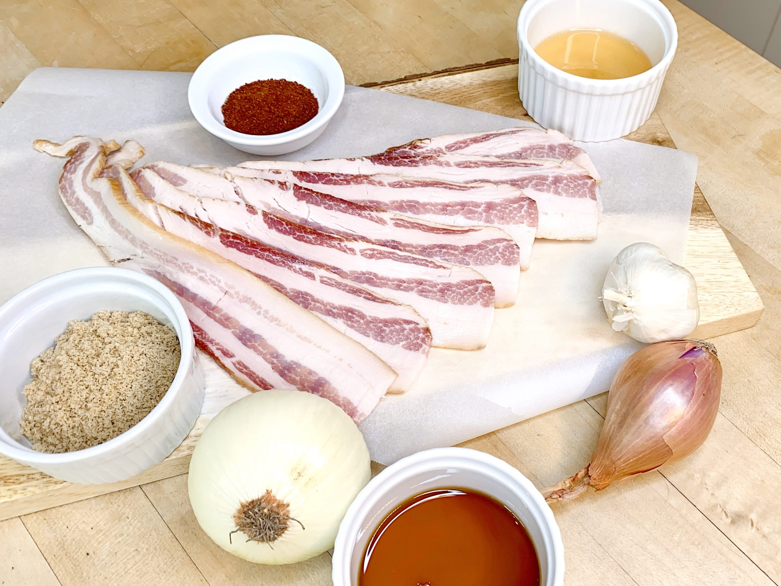 ingredients for making recipe for bacon jam including bacon, onion, shallot, garlic, brown sugar, maple syrup, cider vinegar and chili powder.