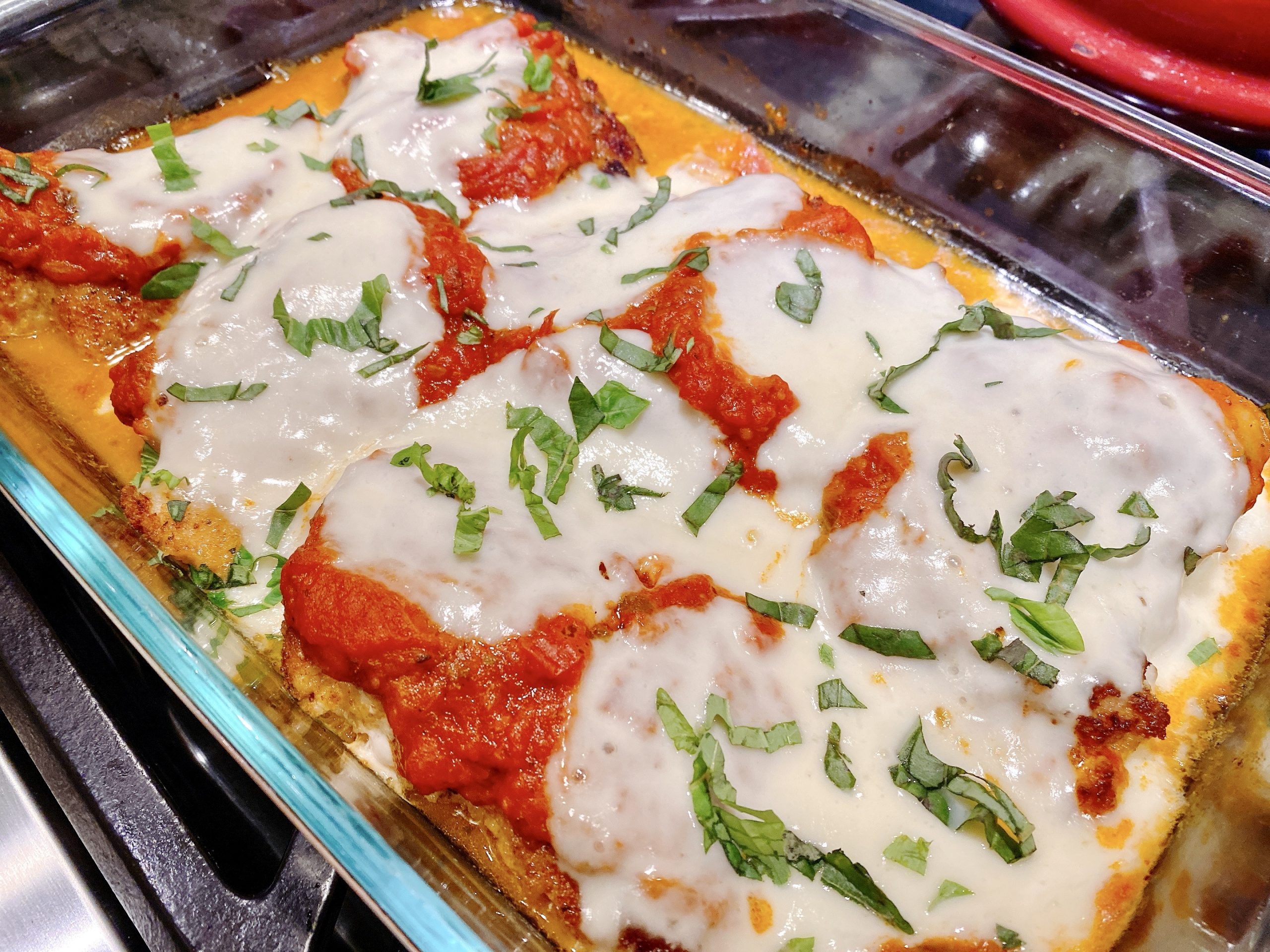 Pan of Chicken Parmesan straight out of the oven with melted cheese and fresh basil.