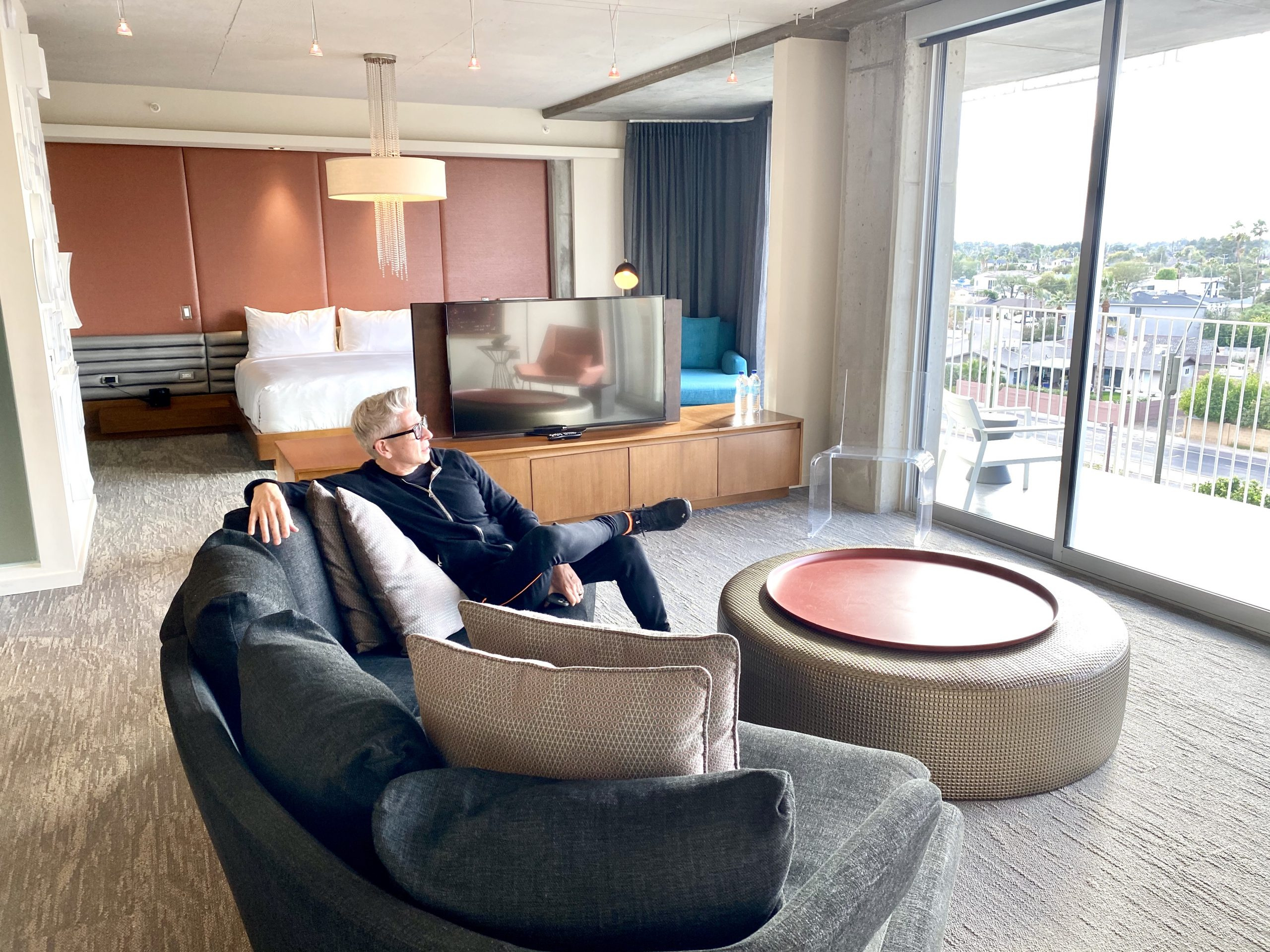 Man enjoys view of Salt River Valley from suite in tower of Hotel Valley Ho in Scottsdale, Arizona