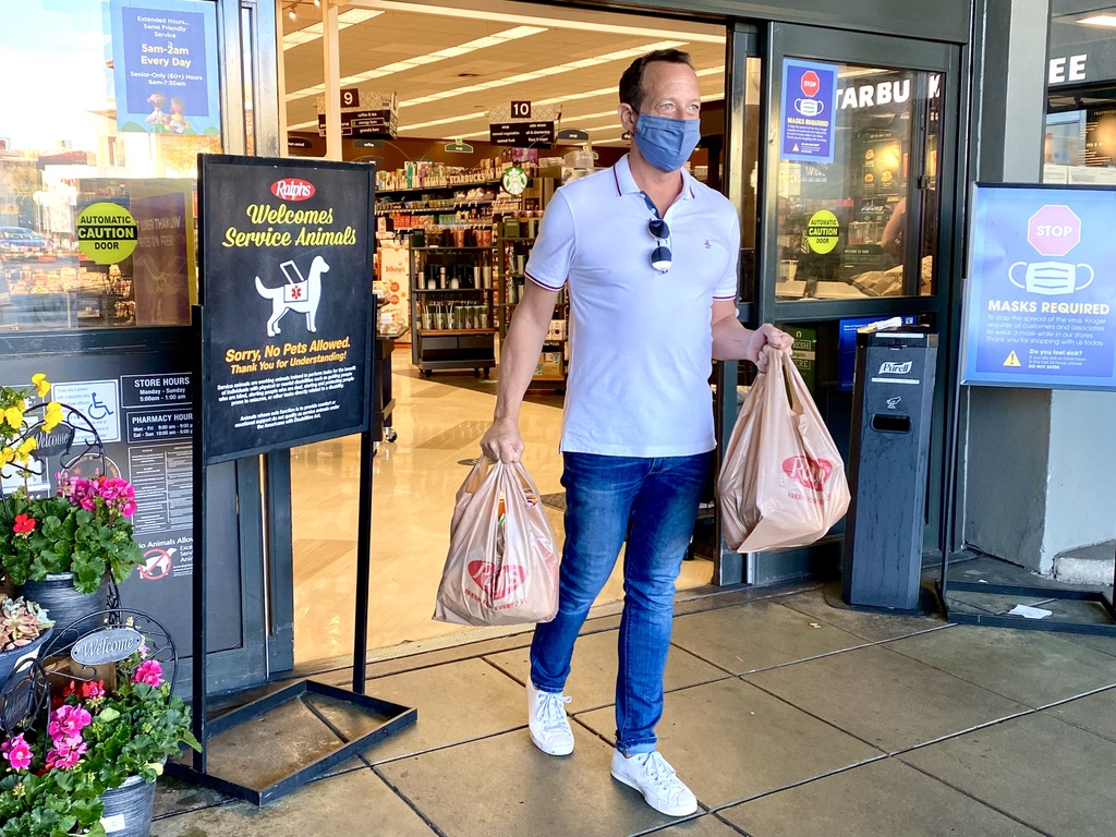 man leaving Ralph's grocery store with bags of groceries