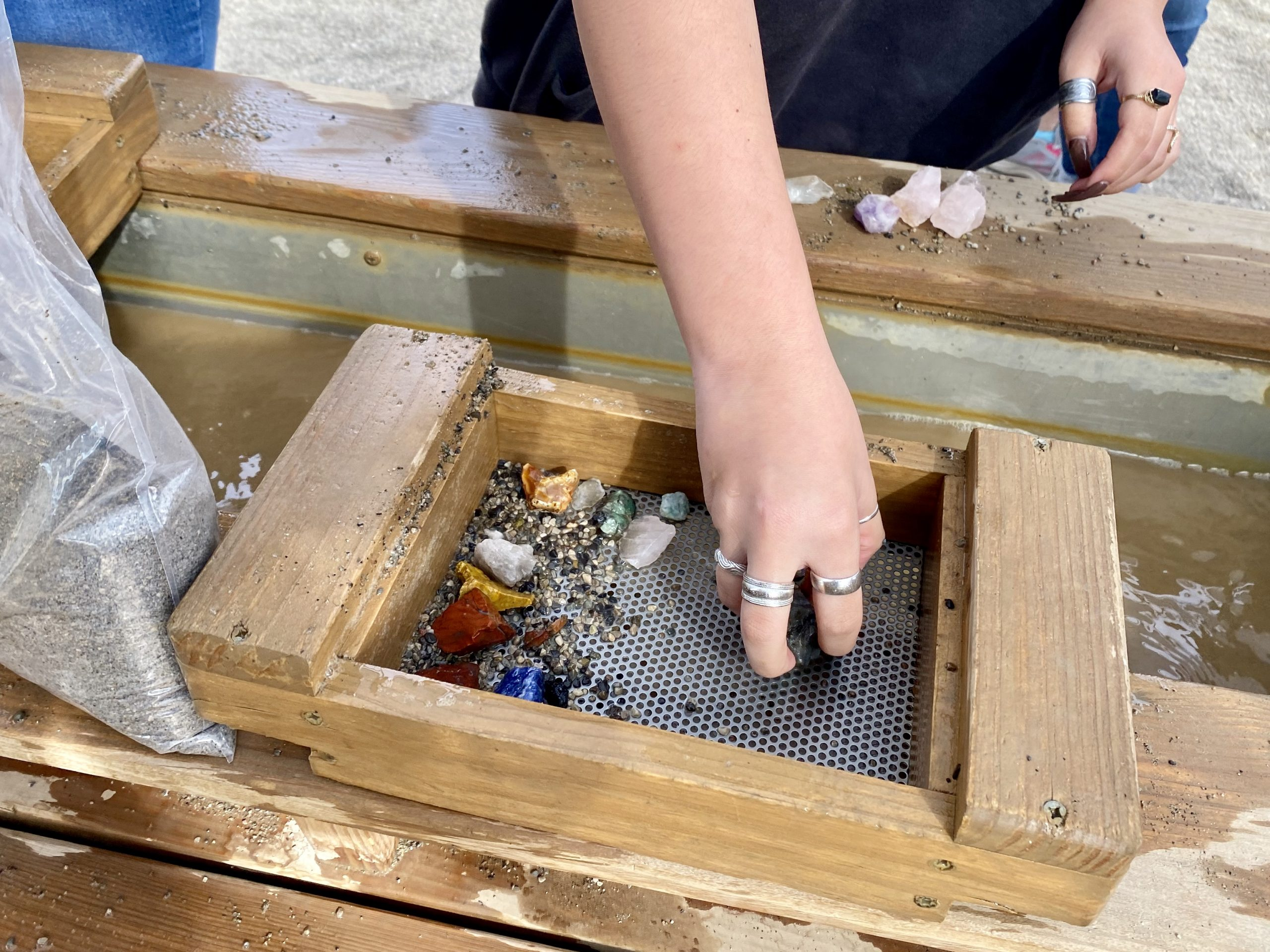 Girl pans for gold and jewels in the water sluice at Goldfield Ghost Town and Mines in Mesa, Arizona