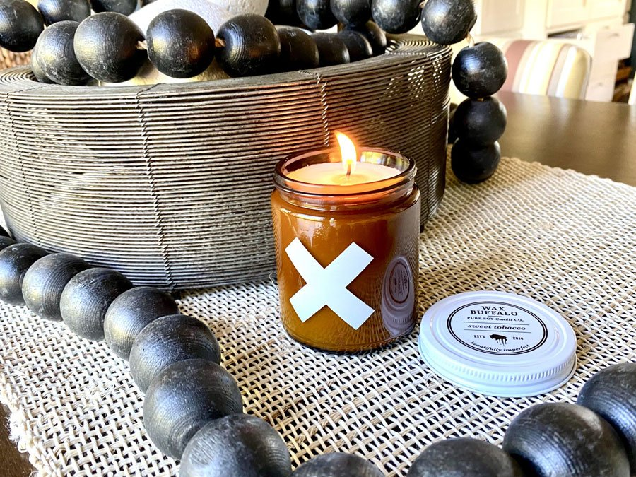 Sweet Tobacco scented Wax Buffalo Soy Candle displayed on table with large black beads