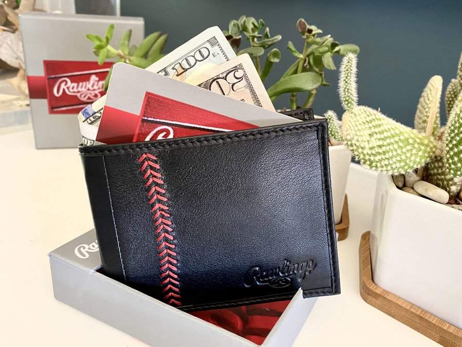 Men's wallet by Rawlings Leather Goods with red baseball stitch displayed with cash and credit card