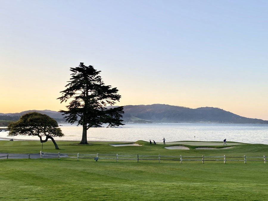 Sunrise at the Lodge at Pebble Beach Resort overlooking the 18th hole of Pebble Beach Golf Links with Carmel Bay in the background.