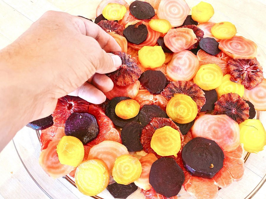 roasted beets and sliced citrus arranged on plate for salad