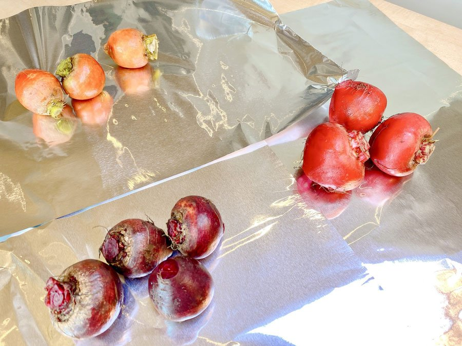 Groups of fresh beets on sheets of tin foil, ready for roasting in pouches.
