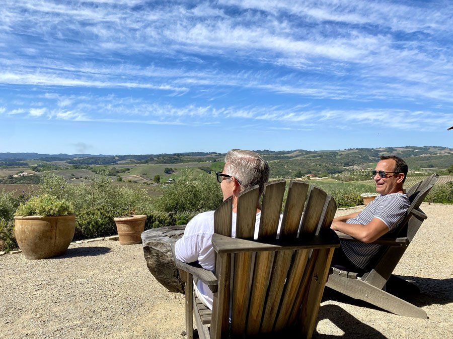 two men sitting in deck chairs enjoying the views of rolling hills in Paso Robles, CA