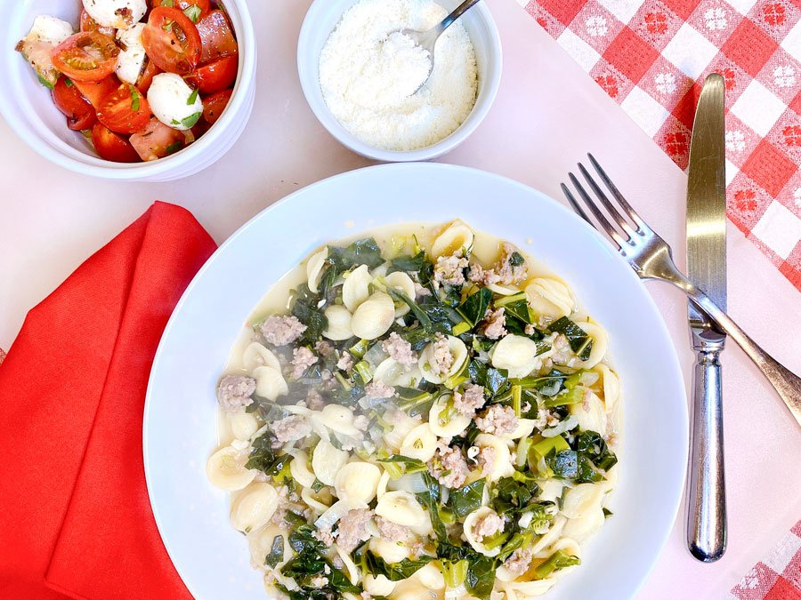 plate of pasta with Italian sausage and broccoli rabe on red checkerboard tablecloth with tomato salad