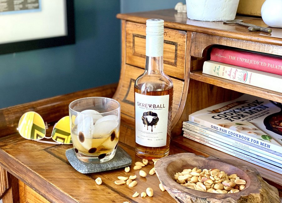 Screwball Peanut Butter Whiskey displayed on antique desk with highball glass and peanuts