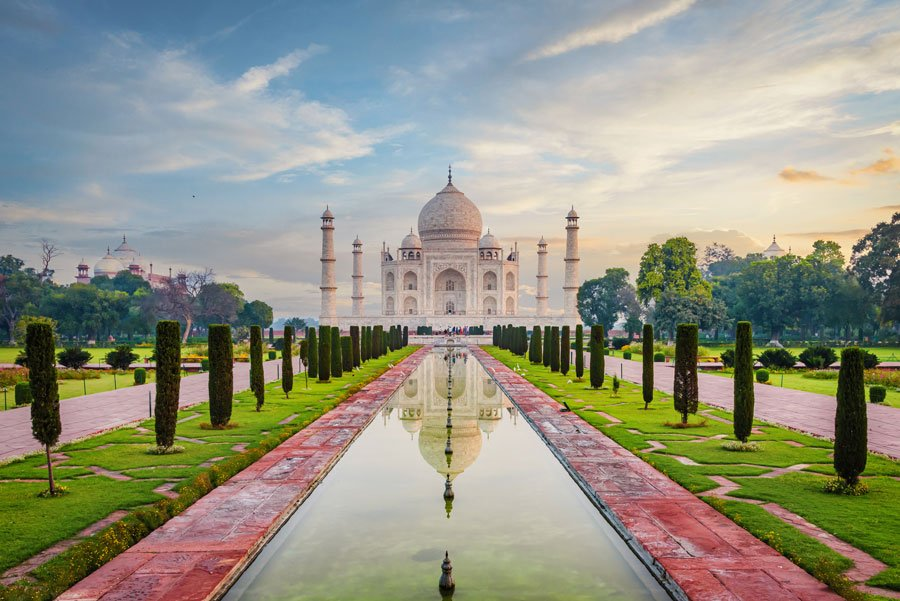 The famous Taj Mahal Mausoleum with reflection in the pond under moody sunrise twilight skyscape. The Taj Mahal is one of the most recognizable structures worldwide and regarded as one of the eight wonders of the world. Agra, India, Asia.