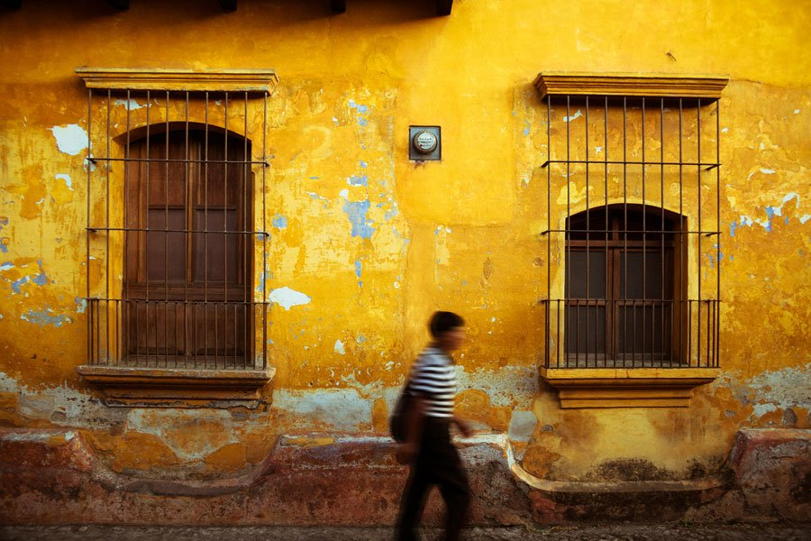 typical antigua guatemala colorful facade while a man on motion blur passes in front