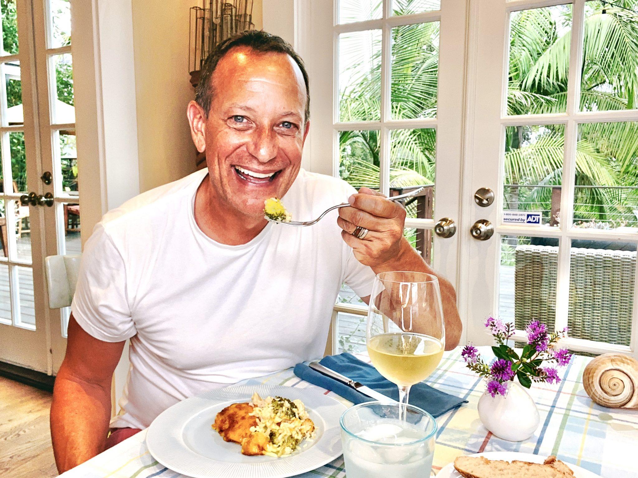 man smiling at camera while sampling Healthy Chicken & Rice Bake with Broccoli Recipe