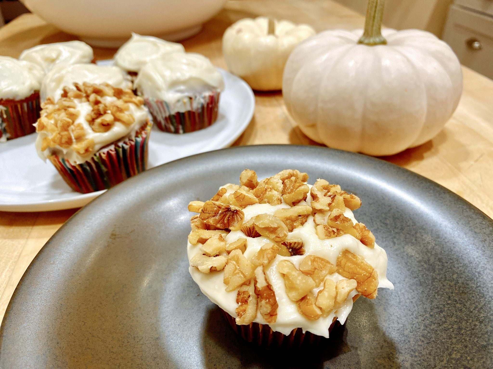 Pumpkin spice cupcake recipe includes cream cheese frosting and chopped walnuts on top.