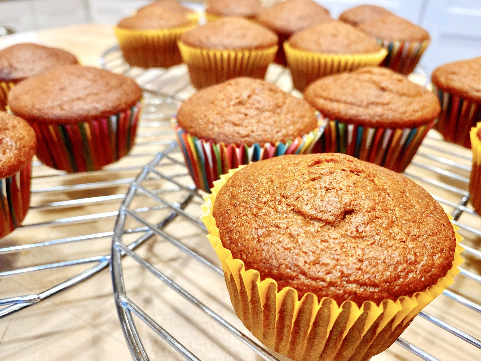 Pumpkin cupcakes freshly baked and cooling on a cooling rack before getting frosted