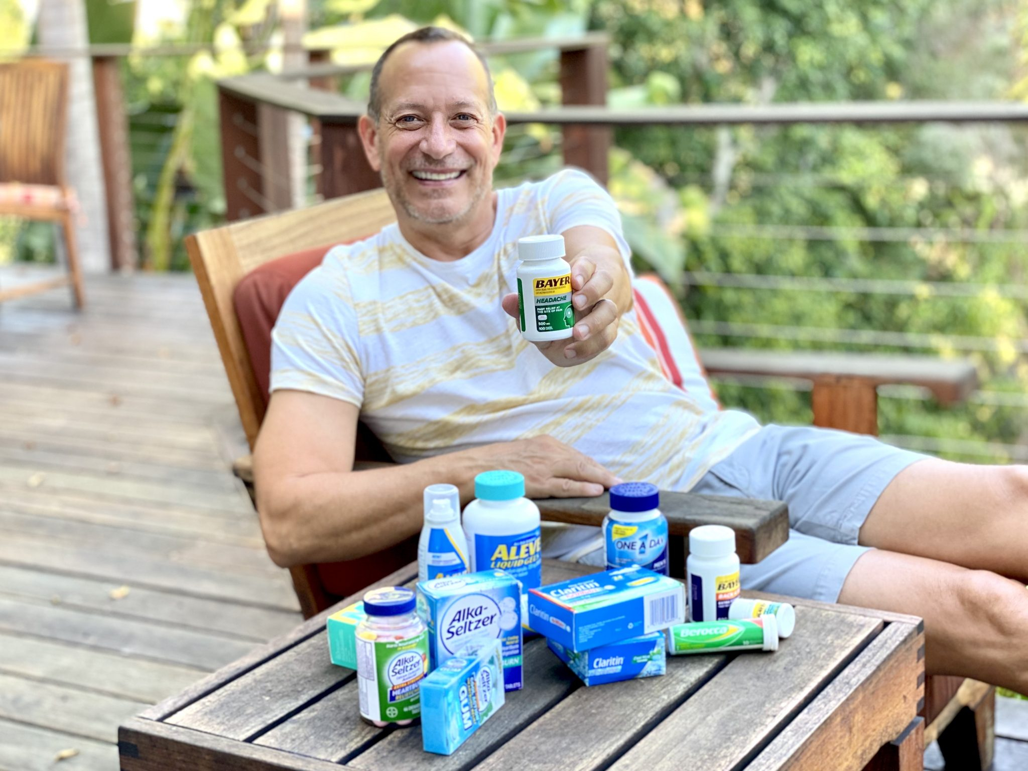 man holding Bayer Headache medication towards camera, with other Bayer products on table next to him