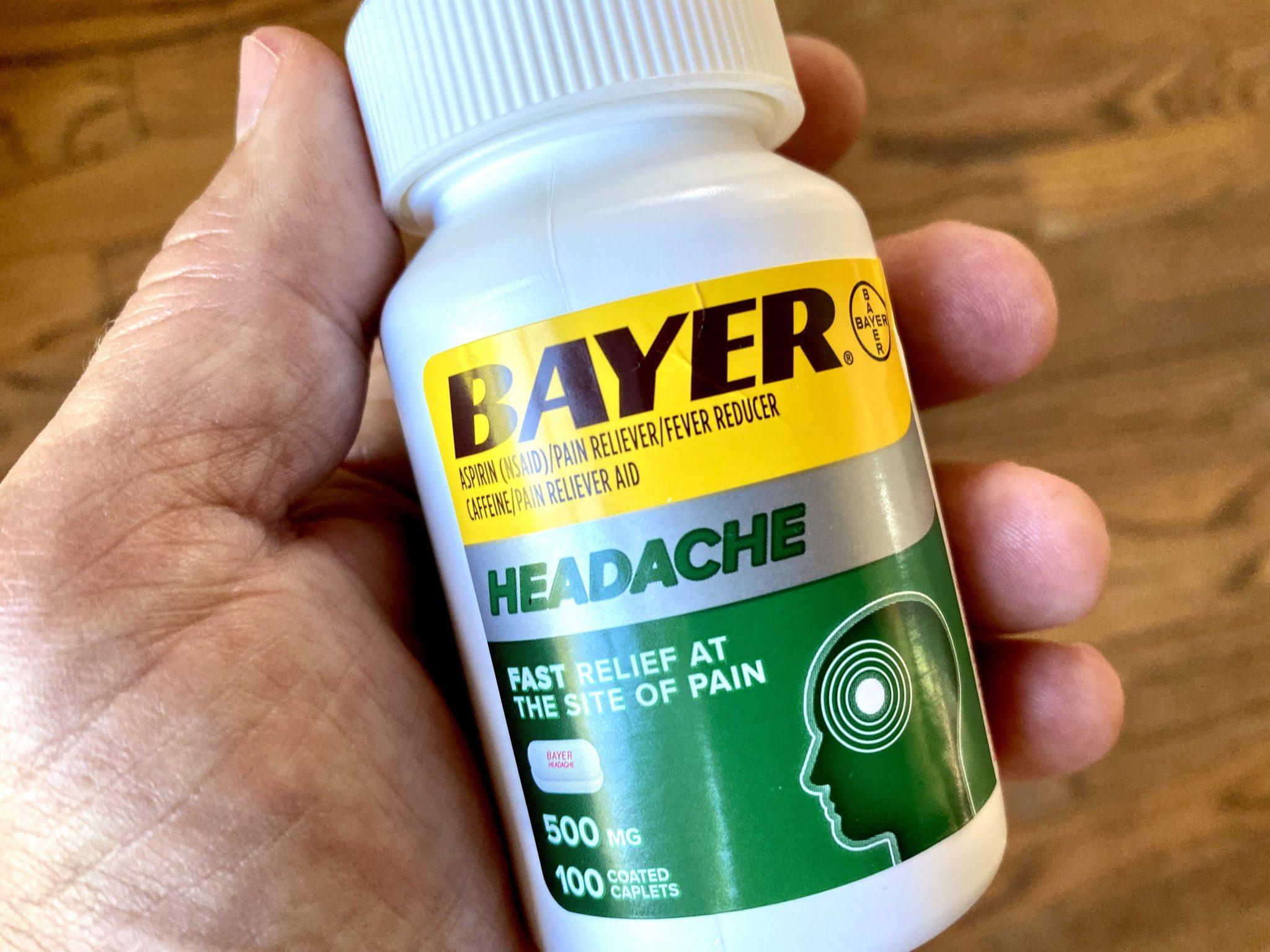 Bayer Headache medication bottle in man's hand