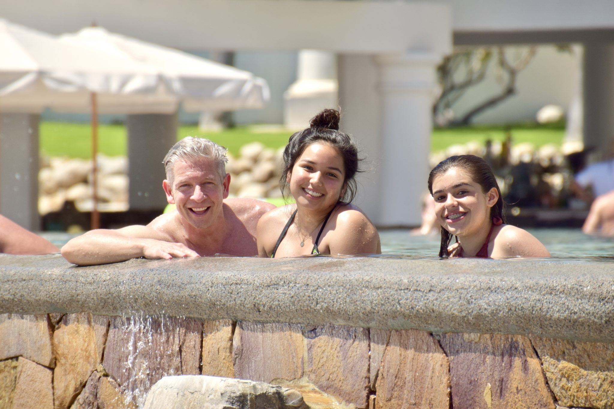 Family smiling over edge of pool at Hilton Los Cabos Resort in Los Cabos, Mexico