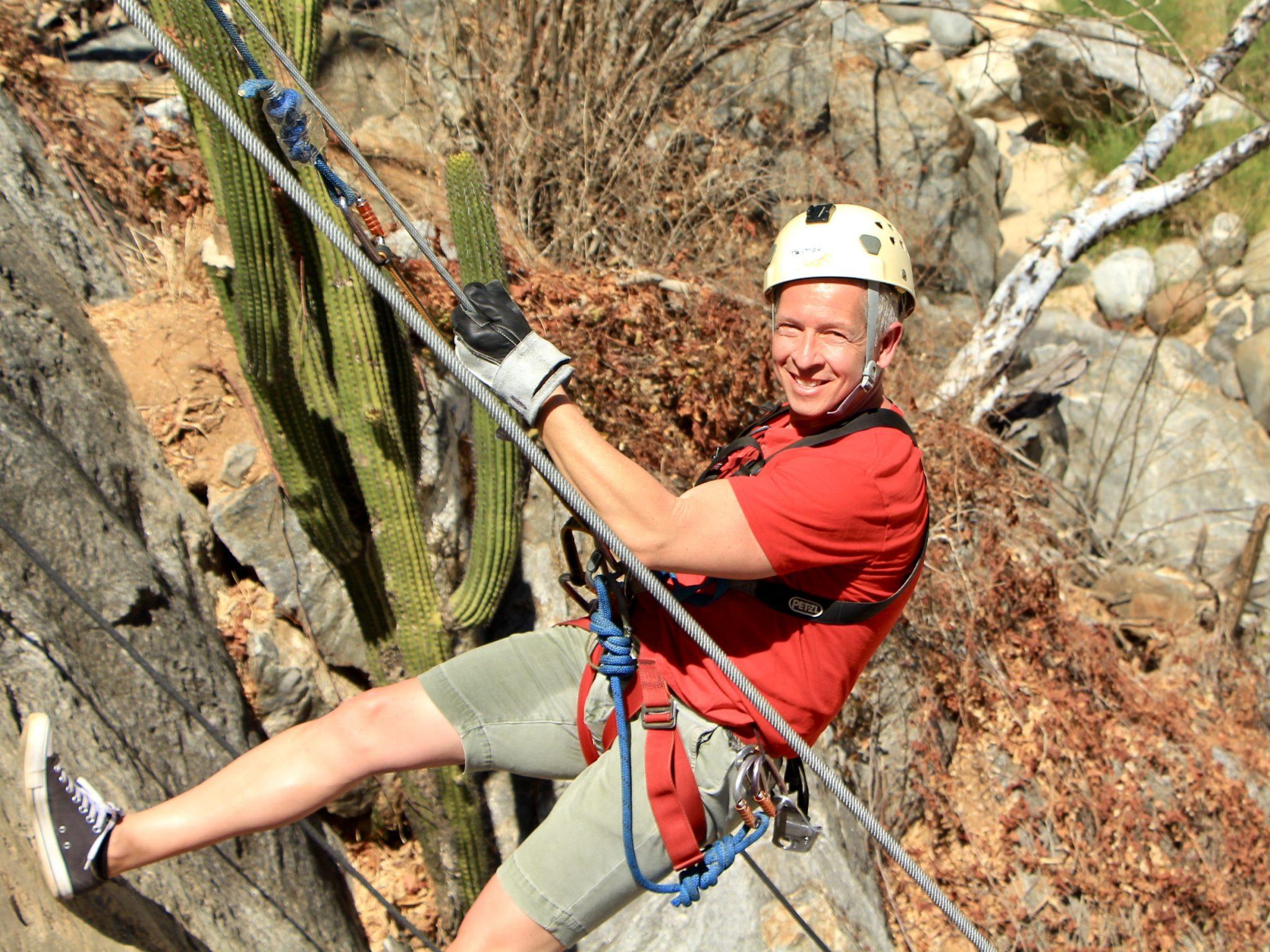 Man rock climbing in gear and helmet with Cabo Adventures in Los Cabos, Mexico