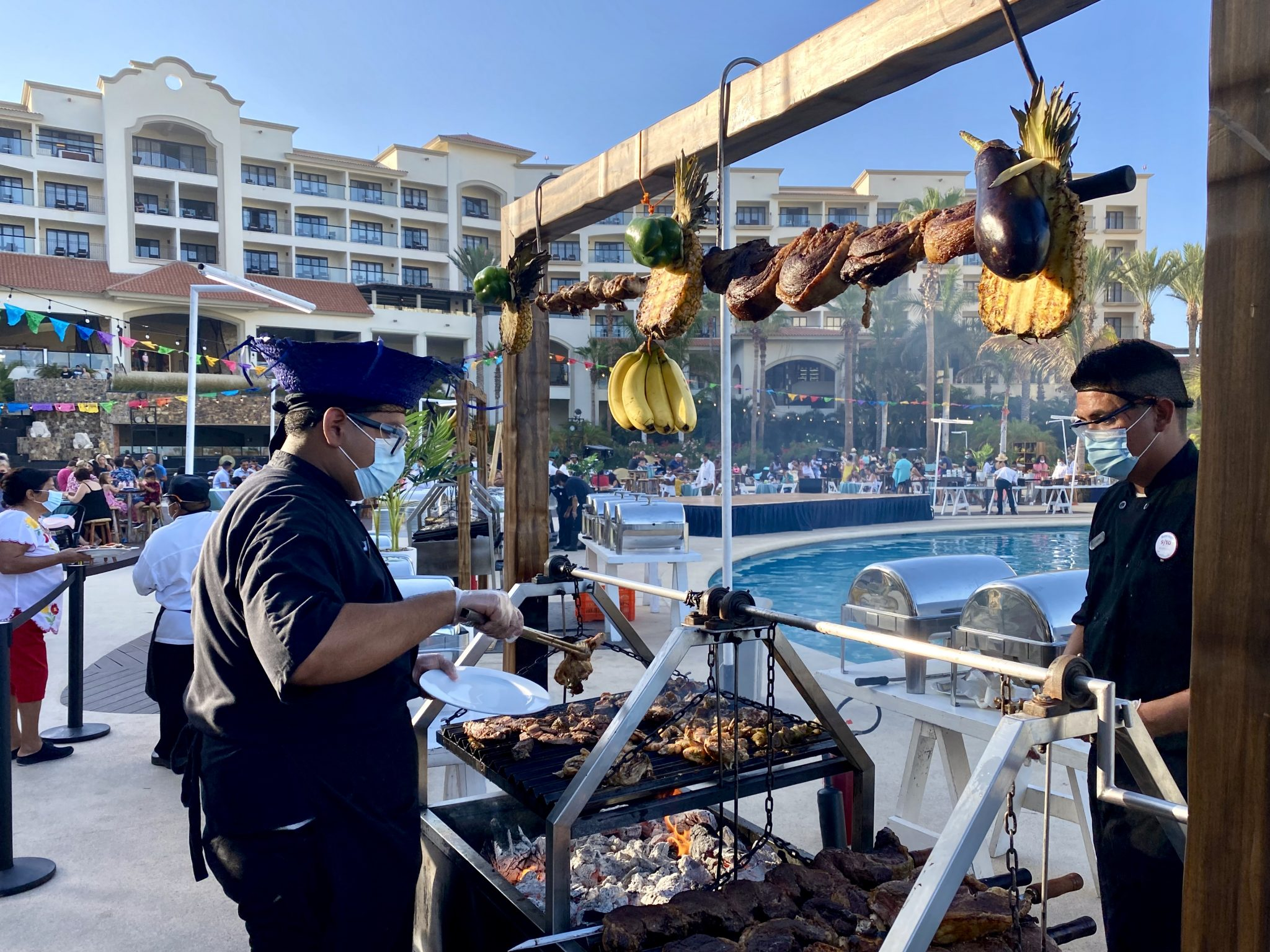 Chefs in masks cooking meats over a hot grill at the Hyatt Riva Resort in Los Cabos, Mexico